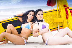 Beach Babes. Two Surfer Beach Babes Lie Back To Back In Bikini While On A Relaxing Surfing Beach Holiday, Yellow Surf Ski In Background Royalty Free Stock Image