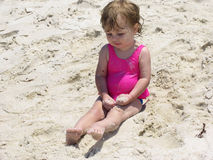 Beach Baby. Baby sitting in the sand on the beach with fistsfuls of sand royalty free stock photo