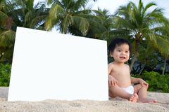 Beach baby. Little baby sitting on beach with a white blank board card Stock Photography