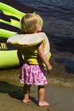 Beach Baby. A toddler in a life jacket stands on the shore watching water skiers Royalty Free Stock Photography
