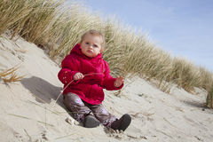 Beach - Baby playing in Sand. Cute blond haired german baby is playing in the sand. babies love to play in sand. blue sky and grasses in the background. red Royalty Free Stock Images