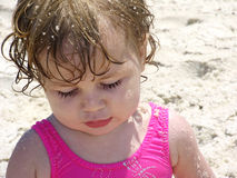 Beach Baby in the Sand. Little girl on the beach with sand in hair royalty free stock photography