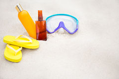 Beach background - flip flops, suntan lotion bottles and diving Royalty Free Stock Photo