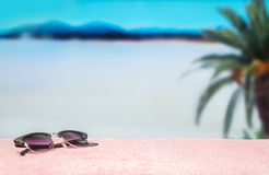 Beach background with free empty blank copy space. Trendy sunglasses on towel in beautiful paradise. Perfect lagoon beach.