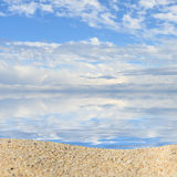Beach background with a heap of sand on a background of sky Stock Images