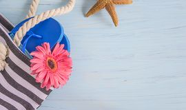Beach bag with blue flip flop, pink gerbera flower and starfish. On blue wooden background top view with copy space royalty free stock photo