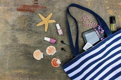 Beach bag, cosmetics and women`s accessories. On old wooden background. Top view Stock Images