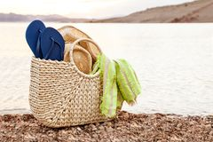 Beach Bag With Flip Flops And Hat For Summer Vacation. At Lake Shore stock images