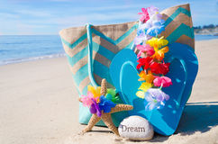 Beach bag with flip flops by the ocean Stock Photos