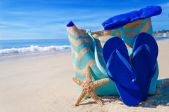 Beach bag with flip flops by the ocean Royalty Free Stock Image