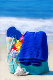 Beach bag with flip flops by the ocean Royalty Free Stock Photo