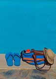 Beach bag and flip flops at the pool Royalty Free Stock Photo