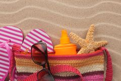 Beach bag with flip flops, sunglasses and sunscreen. Accessories for the beach. View from above stock photo