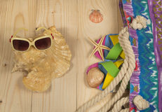 Beach bag, flip flops, sunglasses,  on wooden background. Top view Stock Images