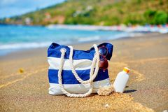 Beach bag, flip flops and sunscreen on beach Royalty Free Stock Images