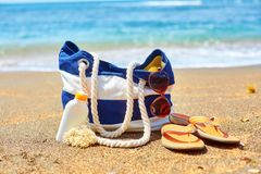 Beach bag, flip flops and sunscreen on beach Royalty Free Stock Photo