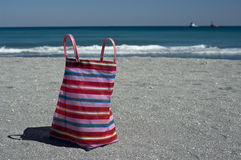 Beach Bag on Florida Beach. Pink, striped beach bag, turquoise water, sandy beach, boats in the distance, Florida Beach Royalty Free Stock Photo
