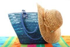 Beach bag with straw hat. On beach towel Stock Photos