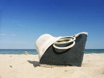Beach bag and straw hat. Beach bag with straw hat on a beach over sea and blue sky Stock Photo