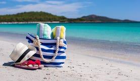 Beach bag, straw hat, flip flops and towel on. Beach bag, straw hat, towel on the white sandy tropical beach Stock Photos