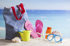 Beach bag, sun glasses and flip flops on a tropical beach stock photos