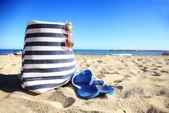 Beach bag sunglasses and hat on the white sandy beach with the blue sky background summer holiday Royalty Free Stock Images