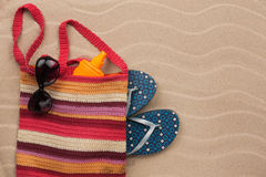 Beach bag with sunscreen, flip flops, sunglasses. Royalty Free Stock Photo