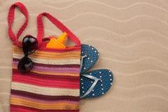 Beach bag with sunscreen, flip flops, sunglasses. Royalty Free Stock Photo