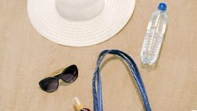 Beach bag, sunscreen, sunglasses and hat on sand stock video