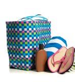 Beach bag with towel, flip-flops and suntan lotion stock photos