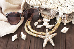 Beach bag with towel, sunglasses  and  hat  on  wooden background Stock Image