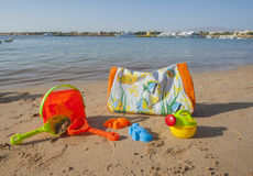 Beach bag and toys on the beach Royalty Free Stock Photo