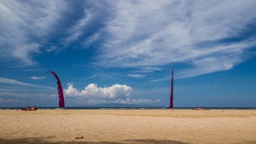 Beach in bali, sanur, sunbathing people and two red flags Stock Image