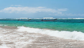 Beach in Bali with sea views with two boats with a line of surf on a Sunny day with clouds on the horizon horizontal Royalty Free Stock Photography