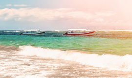 Beach in Bali with sea views with two boats with a line of surf on a Sunny day with clouds on the horizon horizontal view Stock Image