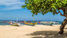 Beach in bali, three boats ready to sail Stock Image