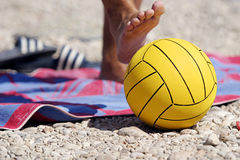 Beach Ball. Yellow ball with players foot over it Royalty Free Stock Image