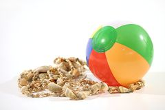 Beach Ball. Small beach ball and sea shells on white background Royalty Free Stock Photos