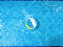 Beach ball che galleggiano sullo stagno Immagine Stock
