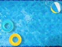 Beach ball ed anelli di nuotata che galleggiano sullo stagno Immagini Stock