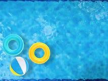 Beach ball ed anelli di nuotata che galleggiano sullo stagno Fotografia Stock