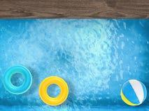 Beach ball ed anelli di nuotata che galleggiano sullo stagno Immagine Stock