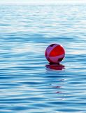 Beach ball floating away on the lake. A inflatable red and white beach ball floats out and away on lake Michigan in the USA stock photography