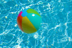 Beach ball floating on pool Royalty Free Stock Images
