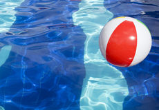 Beach ball floating in swimming pool. Royalty Free Stock Photos