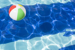 Beach ball floating in swimming pool. Stock Image