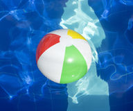 Beach ball floating in swimming pool. Stock Photos