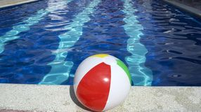 Beach ball floating in swimming pool. Royalty Free Stock Photography