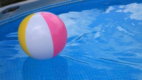 Beach ball floating in swimming pool moving stock footage