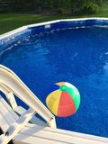 Beach Ball Floats on Surface of Above-Ground Swimming Pool. A multi-coloured beach ball floats on the water of an above-ground swimming pool on a sunny summer Royalty Free Stock Photo